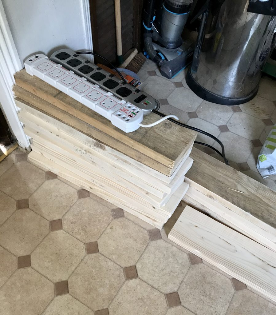 This photo shows the recycled wood, piled up in my kitchen. Some of the wood has been sanded, and some of it hasn't. The difference between the two is very stark!