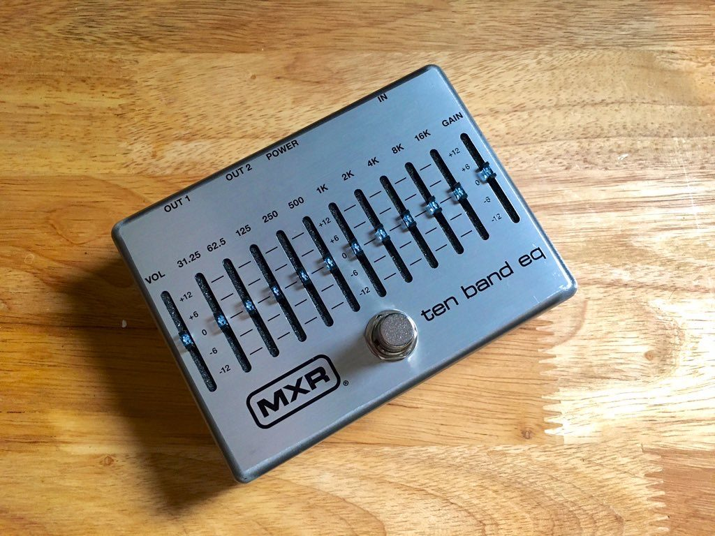 This photos is a top-down shot of the 10 band EQ pedal from MXR. All 10 EQ sliders are shown, along with a volume slider on the far-left, and a gain slider on the far-right of the pedal.