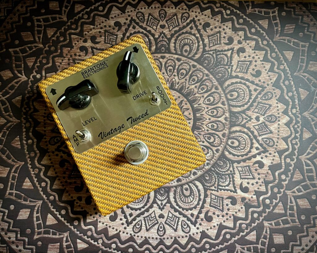 This photo shows a Vintage Tweed pedal by Brantone Electronics. The pedal itself is noticeable because it is covered in the same striped yellow cloth that was used on vintage tweed amps.
