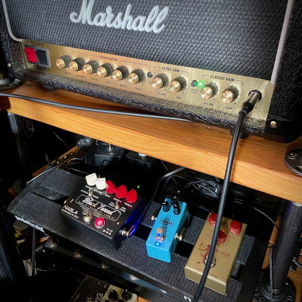 This photo shows my Marshall DSL20HR amp head on a shelf, and my pedal board on a second shelf below.  The Marshall DSL20HR is on the clean channel, and the controls can be seen as follows:  * reverb: off * resonance: about 8 o'clock * presence: about 12 noon * bass: just below 10 o'clock * mids: about 10:30 * treble: about 1:30 * volume: about 10 o'clock * gain: about 11 o'clock  On the pedal board, we can see three pedals: the NABLA Custom Black Tweed, the MXR Sugar Drive, and the JRAD Archer Ikon.