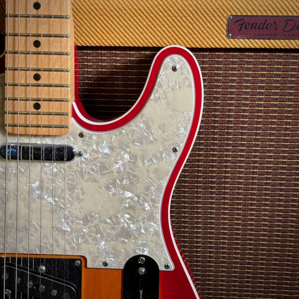 This photo shows a close-up of a Telecaster leaning against the front of a Fender Tweed Deluxe amplifier.  The photo is framed to show both Telecaster pickups, most of the pickguard, and the beginnings of the Telecaster's control plate.
