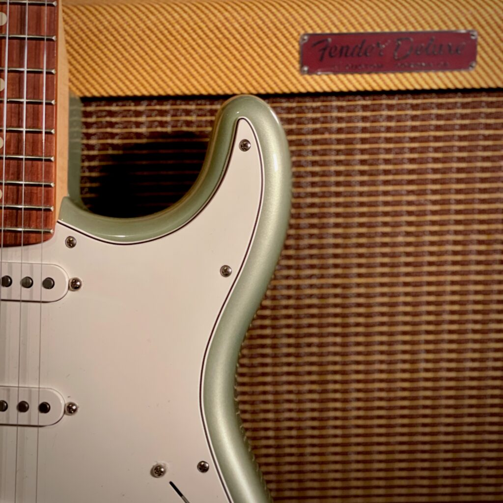This photo shows a close-up of my Fender Player Stratocaster, leaning against the front of the Fender Tweed Deluxe amplifier.